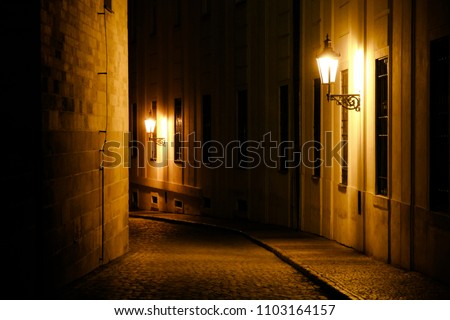 Old lanterns illuminating a dark alleyway medieval street at night in Prague, Czech Republic. Low key photo with brown yellow tones from the lanterns as single light sources against the dark shadows #1103164157