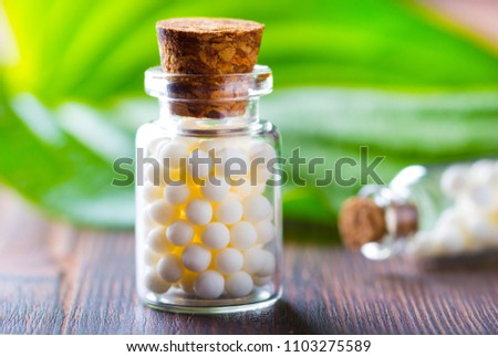 Homeopathy pills bottle wooden eco green leaf background #1103275589