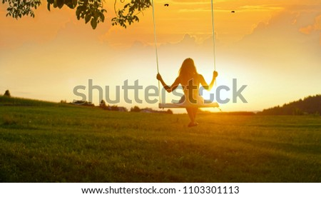 GOLDEN LIGHT SILHOUETTE: Unrecognizable girl in white dress swaying on a tree swing on peaceful evening. Lady sitting on a wooden swing and looking at golden sunset. Young woman swinging at sunrise #1103301113