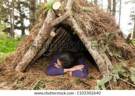 Young woman sleeps in a natural materials survival shelter in the forest #1103302640