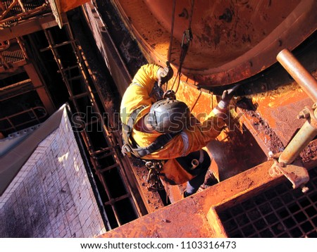 Rope access industrial technician miner fitters, boilermaker wearing fully safety harness, abseiling working maintenance inspecting cleaning chute roller isolated mining iron ore construction Perth #1103316473