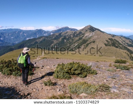 A male hiker in a hat holding trekking poles and walking on a trail. Background is the beautiful alpine landscape of Taiwan with a clear blue sky. #1103374829