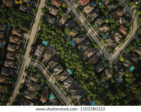 Top down aerial drone image of a suburb in the midst of summer, backyard turf grass and trees lush green.  The roofs and pools look colorful. #1103380322
