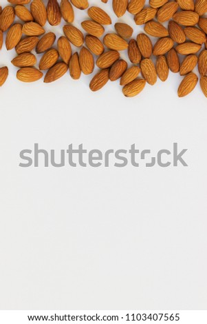 Almonds in bulk on a white background.  Top view, close-up. Copy space. Vertical. #1103407565