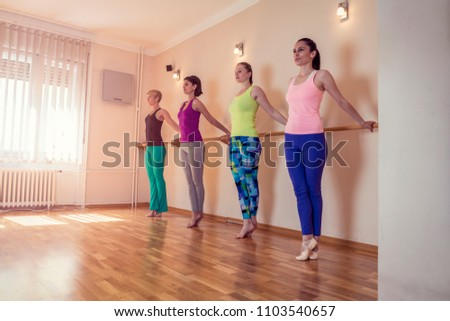 Beautiful adult women doing stretching exercises on Pilates class. Group of females doing yoga, pilates and fitness exercise indoors in studio. #1103540657
