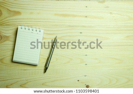 A Notepad on a Wooden Table #1103598401