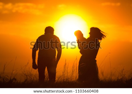 Dad and mom raise the baby in the air, the family has fun - silhouette #1103660408