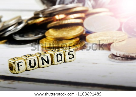 Dice with word FUNDS and coins on wooden background. Funding and business concept. Shallow DOF. #1103691485
