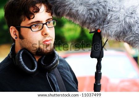 A sound man on a movie set holding a boom mic with a wind sock on it and wearing headphones.