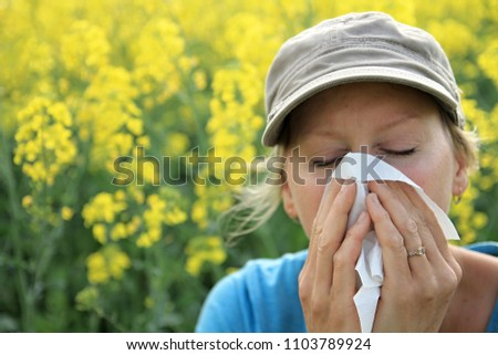 woman sneezing because of pollen woman blowing her nose with yellow background stock image and stock photo #1103789924