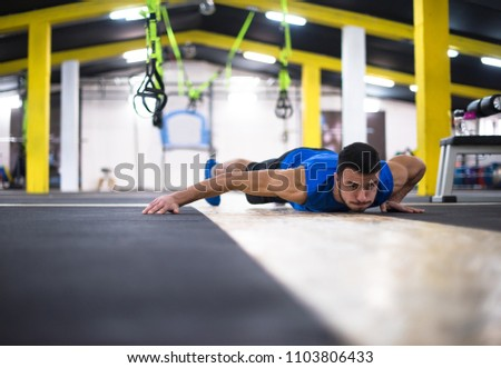 Young strong man doing pushups  at cross fitness gym #1103806433