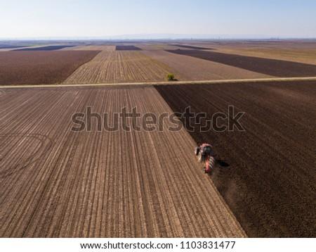 Aerial shot of a farmer plowing stubble field #1103831477