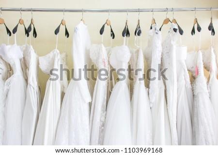 white wedding dresses hanging on racks #1103969168