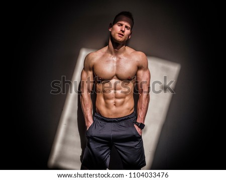 Attractive shirtless blond male bodybuilder in shorts indoors in dark gym, showing muscular torso and ripped abs #1104033476