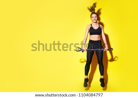 Young happy fitness girl with sporty body posing at studio on a yellow background. Beautiful fit Girl. Fitness smiling model in black sportswear. Weight Loss. Healthy lifestyle. Sporty healthy female. #1104084797