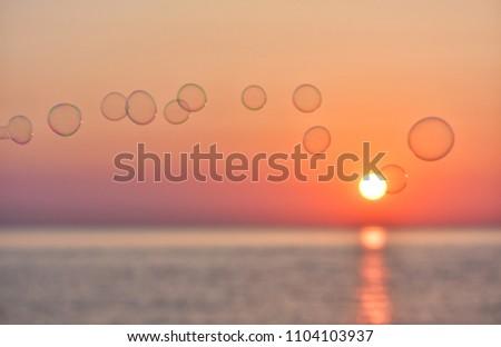 soap bubbles on sunrise background- sunrise over the baltic sea in gdynia, poland #1104103937