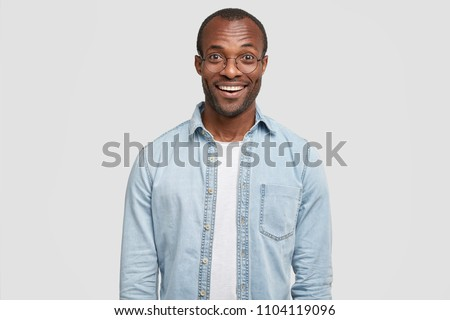 Waist up shot of delighted dark skinned male with bristle, smiles positively, being satisfied after job interview, dressed in denim shirt, stands against white background. Happiness and ethnicity #1104119096