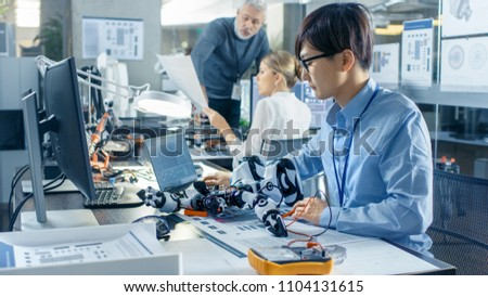Electronics Engineer Works with Robot, Manipulating its Responses and Checking Data with Laptop Computer. Computer Science Research Laboratory with Specialists Working. #1104131615