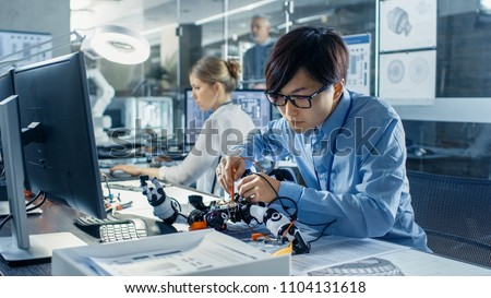 Electronics Engineer Works with Robot Checking Voltage and Program Response time. Computer Science Research Laboratory with Specialists Working. #1104131618