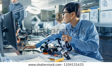 Electronics Engineer Works with Robot Checking Voltage and Program Response time. Computer Science Research Laboratory with Specialists Working. #1104131633