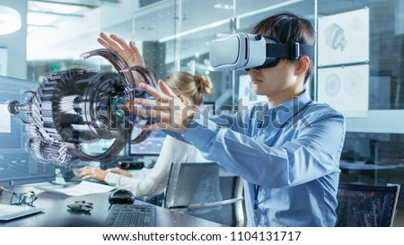 Computer Science Engineer wearing Virtual Reality Headset Works with 3D Model Hologram Visualization, Makes Gestures. In the Background Engineering Bureau with Busy Coworkers. #1104131717
