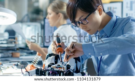 Electronics Engineer Works with Robot, Soldering Wires and Circuits. Computer Science Research Laboratory with Specialists Working. #1104131879