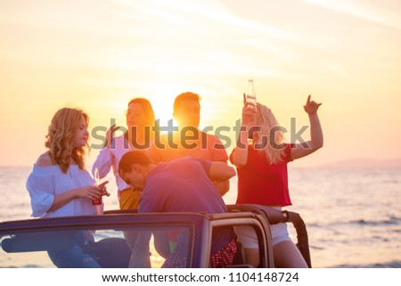 young people having fun in convertible car at the beach at sunset. #1104148724
