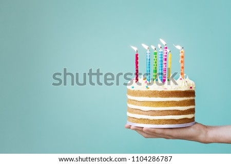 Birthday cake with buttercream and colorful candles Royalty-Free Stock Photo #1104286787