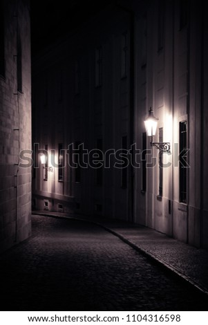 Old lanterns illuminating a dark alleyway medieval street at night in Prague, Czech Republic. Monochromatic photo in vertical format. #1104316598