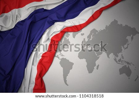 waving colorful national flag of thailand on a gray world map background.