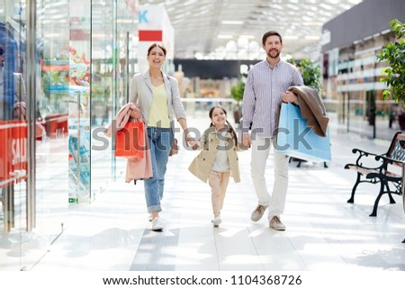 Happy family of shoppers enjoying leisure in large modern trade center on weekend #1104368726