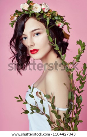 Woman bright summer look beautiful clothes. Flowers wreath on head. Brunette girl posing and smiling on bright pink background. Lady with flowers in her hands, young sexy model in beautiful