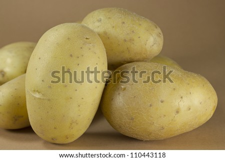 Group of potatoes on a brown background.