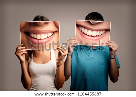 happy couple holding a picture of a mouth smiling on a gray background
