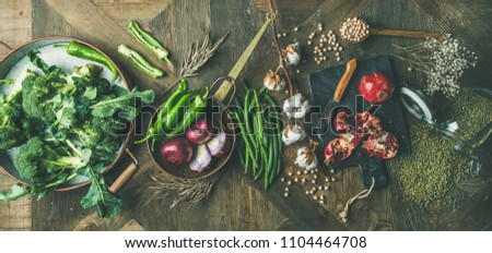 Winter vegetarian, vegan food cooking ingredients. Flat-lay of seasonal vegetables, fruit, beans, cereals, kitchen utencils, dried flowers, olive oil over wooden background, top view, wide composition #1104464708