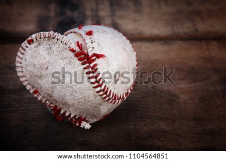 Image of a well loved baseball splitting at the seams forming a heart shape