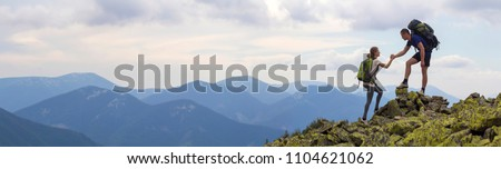 Young tourists with backpacks, athletic boy helps slim girl to clime rocky mountain top against bright summer sky and mountain range background. Tourism, traveling and healthy lifestyle concept. #1104621062