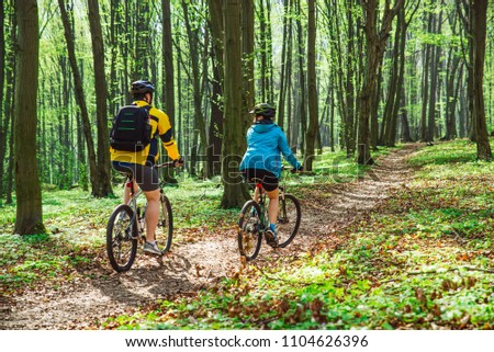 couple riding bicycle in forest in warm day. view from behind #1104626396