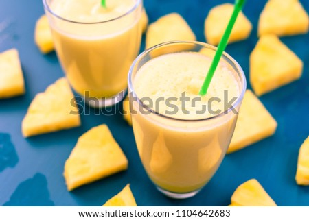 Pineapple smoothie with fresh pineapple on wooden blue table. #1104642683