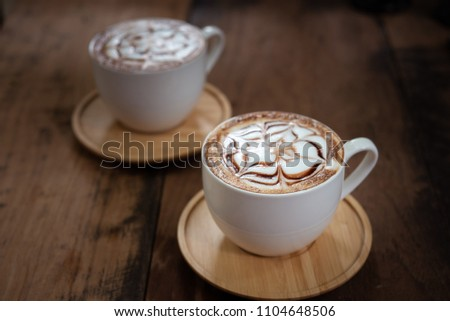 Two cups of coffee on black rustic background with beautiful latte art. Cup of coffee on a wooden table #1104648506