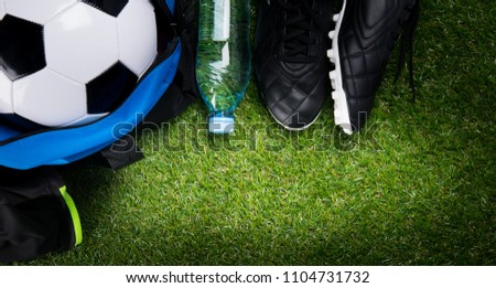 soccer ball, in a sports bag, a bottle of water and black boots, against the background of grass #1104731732
