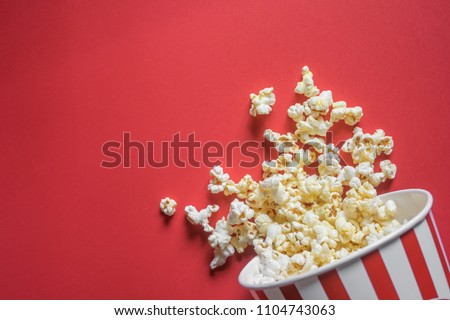 Spilled popcorn on a red background, cinema, movies and entertainment concept #1104743063