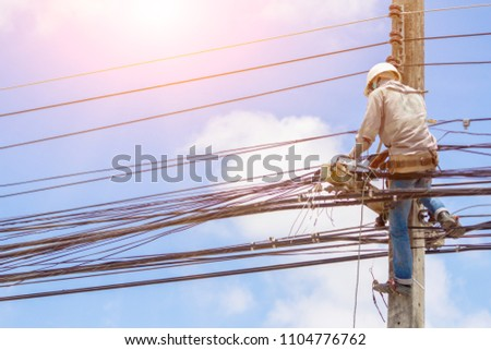 The electrician was climbing up the power poles to perform maintenance work on a protective suit, and a white helmet that protected the head from falling off of tools on a bright blue sky background. #1104776762
