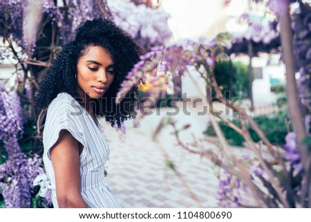 Thoughtful young black woman sitting surrounded by flowers #1104800690