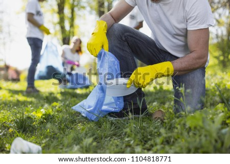 Green living. Close up of male hands wearing yellow gloves and using garbage bag #1104818771