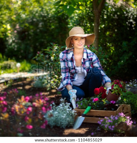 Beautiful female gardener looking at camera smiling and holding wooden crate full of flowers ready to be planted in her garden. Gardening concept. #1104855029