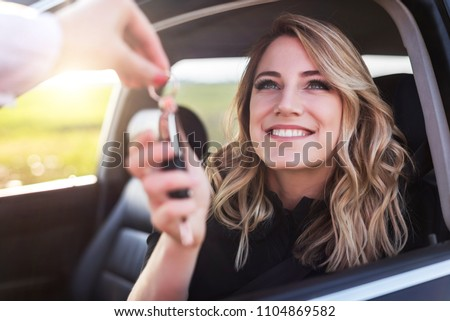 An attractive woman in a car gets the car keys. Rent or purchase of auto - concept. Royalty-Free Stock Photo #1104869582