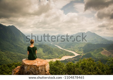 Girl with green shirt sitting on a rock on top of a mountain watching the beautiful scenery of the backcountry of Nong Khiaw, Laos. Location: Viewpoint in Nong Khiaw.  #1104878465