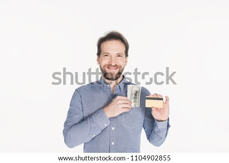 portrait of smiling bearded man with dollar banknotes in pocket showing credit card in hand isolated on white #1104902855