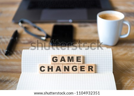 Closeup on notebook over wood table background, focus on wooden blocks with letters making Game Changer text. Concept image. Laptop, glasses, pen and mobile phone in defocused background